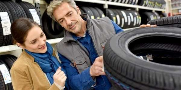 man and woman look at new tires
